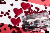 Cassette audio audio sur un arrière-plan rouge avec coeur de tissu — Photo
