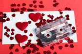 Audio cassette tape on red background with fabric heart — Stock Photo