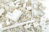 Scattered keyboard keys on white — Stock Photo