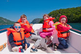 Kids in lifejackets in a boat — Stock Photo