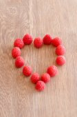 Raspberry in a shape og heart on wooden background — Stock Photo