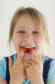 The smiling girl with raspberries in her mouth — Stock Photo