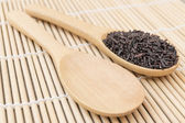 Black rice organic put on the wooden spoon — Stock Photo
