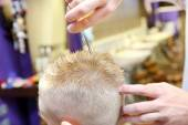 Hairdresser trimming blonde hair of young boy by scissors — Stock Photo