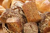 Wicker basket with wholegrain bread and rolls — Stock Photo