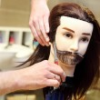 Barber student trimming brown hair using puppet and scissors — Stock Photo #52428249