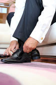 Groom dresses and binds shoes before the wedding — Stock Photo