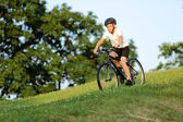 Teenage boy rides a bike from the hill in city park — Zdjęcie stockowe