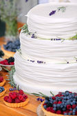Wedding cake on wooden background with blueberries raspberries a — Stock Photo