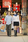 Loving couple at the shopping center with bags — Stock Photo