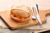 Sandwich with smoked salmon and dill wrapped in baking paper on  — Stock Photo