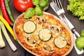 Casserole with zucchini and mushrooms on a wooden background — Stock Photo