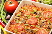 Casserole with tomato and mushrooms on a wooden background — Stock Photo