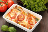 Cannelloni baked in a roasting pan on a wooden background — Stock Photo