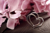 Two linked silver hearts on a plank on a floral background in vi — Stock Photo