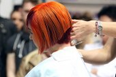 POZNAN - APRIL 18 : Hairdresser trimming red hair with scissors — Stock Photo