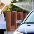 Young boy washing the car with hose — Stock Photo #74162821