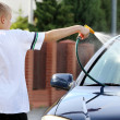 Young boy washing the car with hose — Stock Photo #74162807