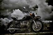 Vintage motorcycle under storm clouds — Stock Photo