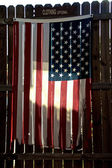 Tattered american flag on fence — Stock Photo