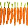 Line of organic carrots with green tops over white — Stock Photo #66966277