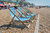 4 deck chairs on Brighton beach — Stock Photo