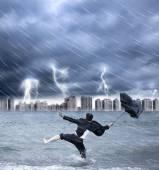 Businessman holding an umbrella with thundershower — Stock Photo