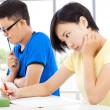 Two young college students sitting an exam in a classroom — Stock Photo #52255667