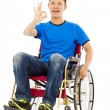 Happy young man sitting on a wheelchair and ok gesture — Stock Photo #52327219