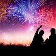 Happy family sitting on floor and watching the fireworks — Stock Photo