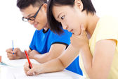 Two young students exams together in classroom — Stock Photo