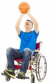 Young man sitting on a wheelchair and holding a basketball — Stock Photo