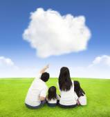 Happy family on a meadow with cloud background — Stock Photo