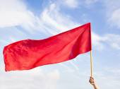 Hand waving a red flag with blue sky background — Stock Photo