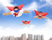Superman and daughters  flying in the sky — Stock Photo
