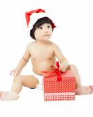 Adorable baby in Santa cap sitting on floor with christmas gift — Stock Photo