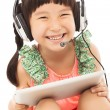 Closeup of happy little student girl holding a tablet — Stock Photo #53683767