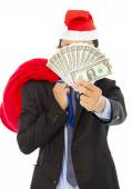 Business man holding a christmas gift bag and money  — Foto de Stock