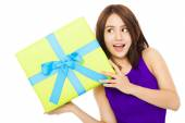 Happy young woman holding a gift box over white background — Stock Photo