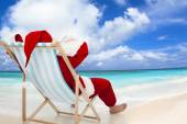 Santa Claus sitting on beach chairs with blue sky and cloud — Stock Photo