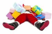 Santa claus too tired to lie on floor with many gift boxes — Stock Photo