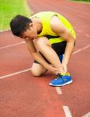 Young male runner with ankle injury on track — Foto Stock