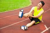 young male runner suffering from leg cramp on the track — Stock Photo