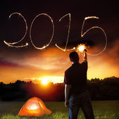 Happy new year 2015. young man drawing 2015 by sparkling stick. — Stock Photo