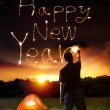 Young man drawing happy new year words by sparkling stick. — Stockfoto