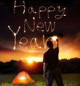 Young man drawing happy new year words by sparkling stick. — Stock Photo