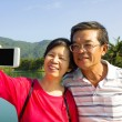 Senior couple taking picture by themselves in outside — Stock Photo #55757241
