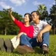 Asian Senior couple sitting on grassland and  taking picture — Stock Photo #55757259