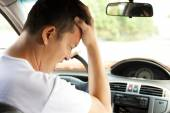 Tired young man have a headache while driving car — Stock Photo