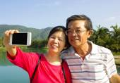 Senior couple taking picture by themselves in outside — Stockfoto